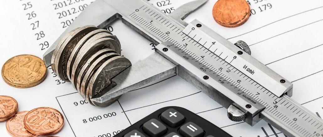 Taschenrechner, Münzen und Kalkulation: Einsparungen, um Schulden loszuwerden