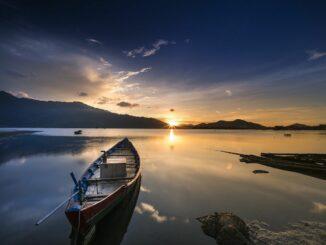 Ein Boot in einem See plus Sonnenuntergang: Seelenruhe ist dank Verzicht und Askese möglich!