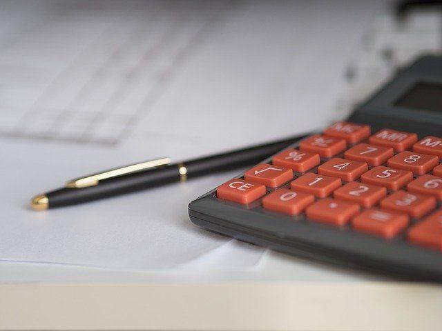 Taschenrechner mit roten Tasten und Kugelschreiber auf Blatt Papier