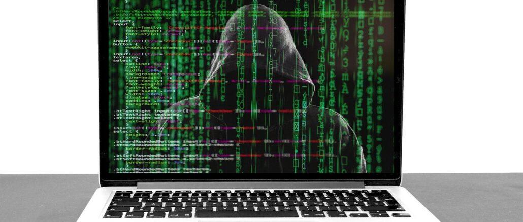Laptop mit einem Hacker und Codes auf dem Bildschirm: Sparkasse Phishing Mails haben Konjunktur!