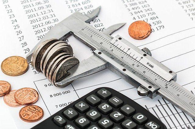 Taschenrechner, Geldmünzen und Papier mit Zahlen: Umschuldungsrechner zur Ermittlung, ob Sie Ihren Kredit umschulden sollten!