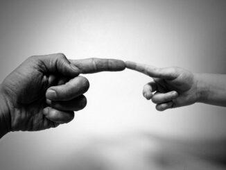 Finger eines Erwachsenen und Finger eines Kindes, die sich berühren: Sparen für den Nachwuchs kann sehr sinnvoll für Ihr Kind / Ihre Kinder sein!